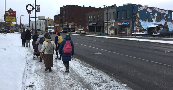 Folks walking on a snowy sidewalk next to a cleared road