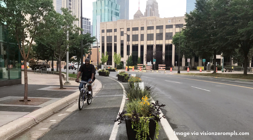 Person biking in 3rd Ave S planter protected bikeway