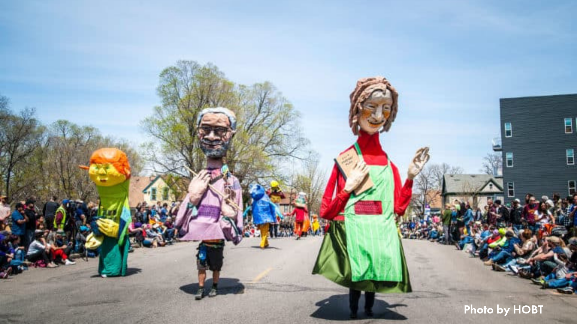 Image of three large puppets parading on the street
