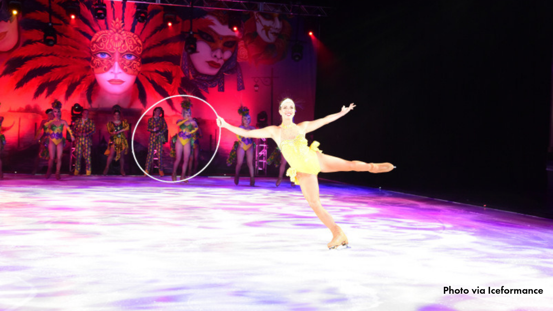 One ice skater performing with bright pink lights