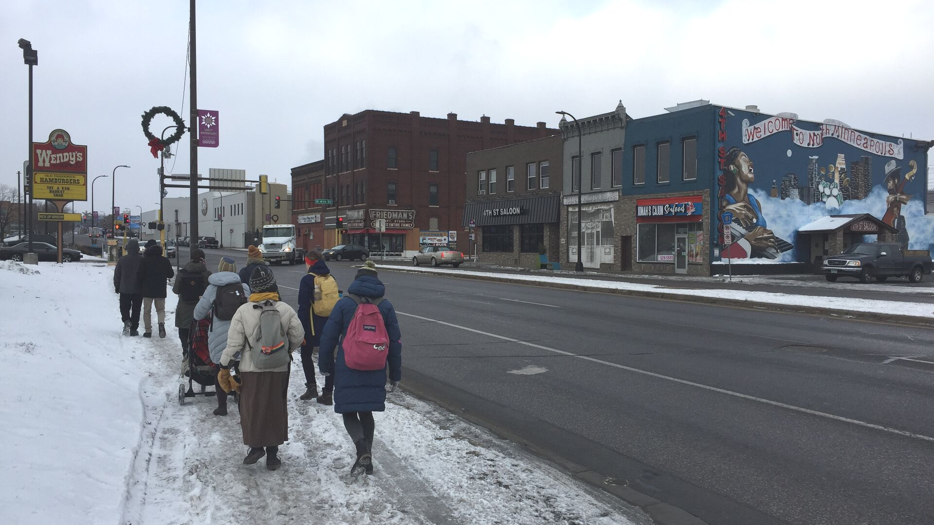 Our Streets MPLS board members walking on a snowy sidewalk