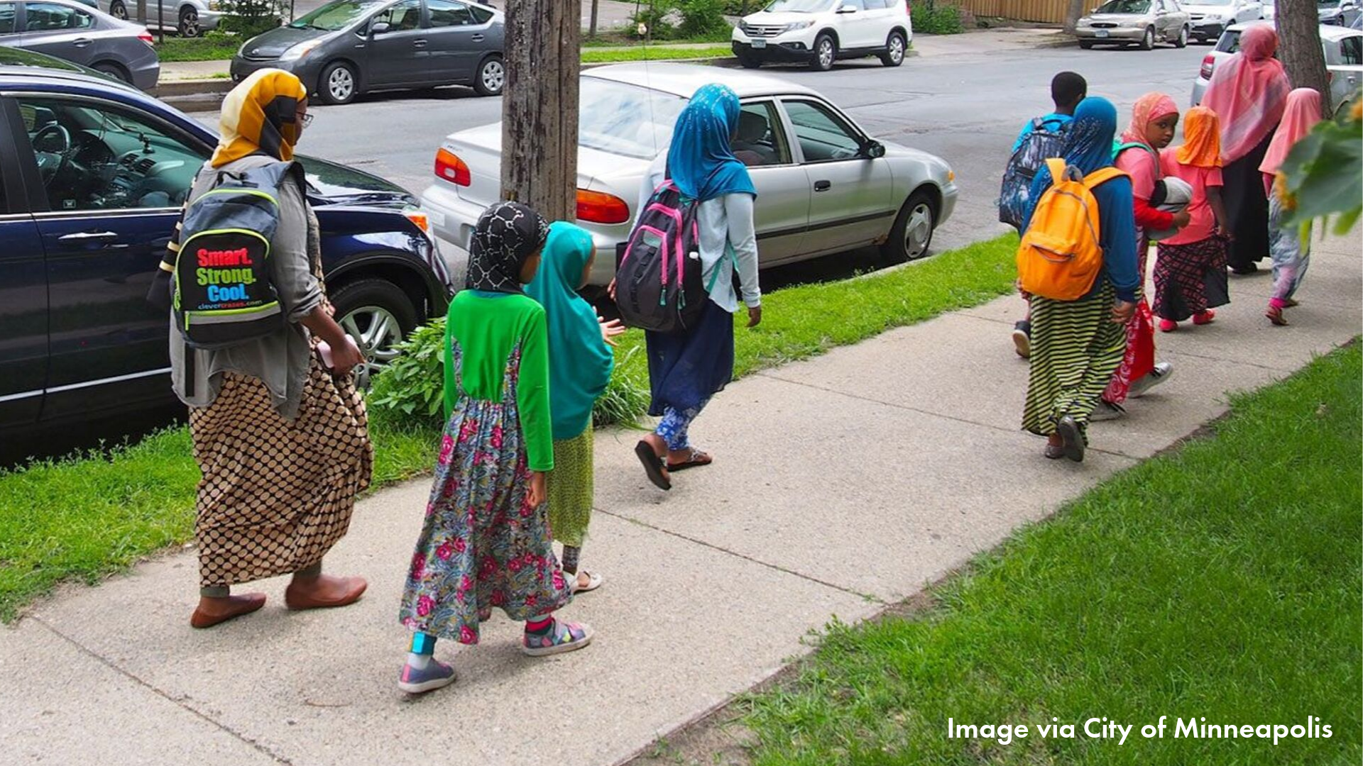 East African adults and children walking on a sidewalk