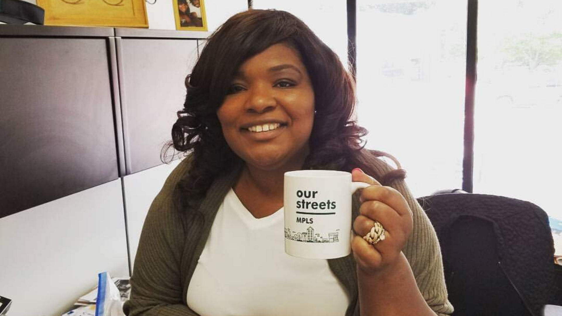 LaTrisha Vetaw at a desk holding an Our Streets Mpls mug