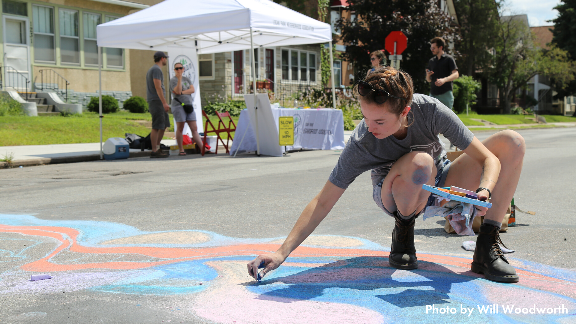 Person drawing a crosswalk in chalk at an Open Streets MPLS event