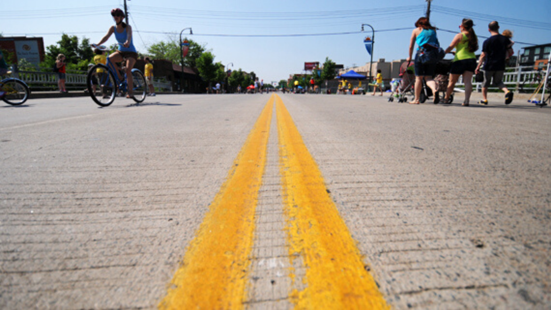 Close up of double yellow center line on open street. People biking & walking in the distance