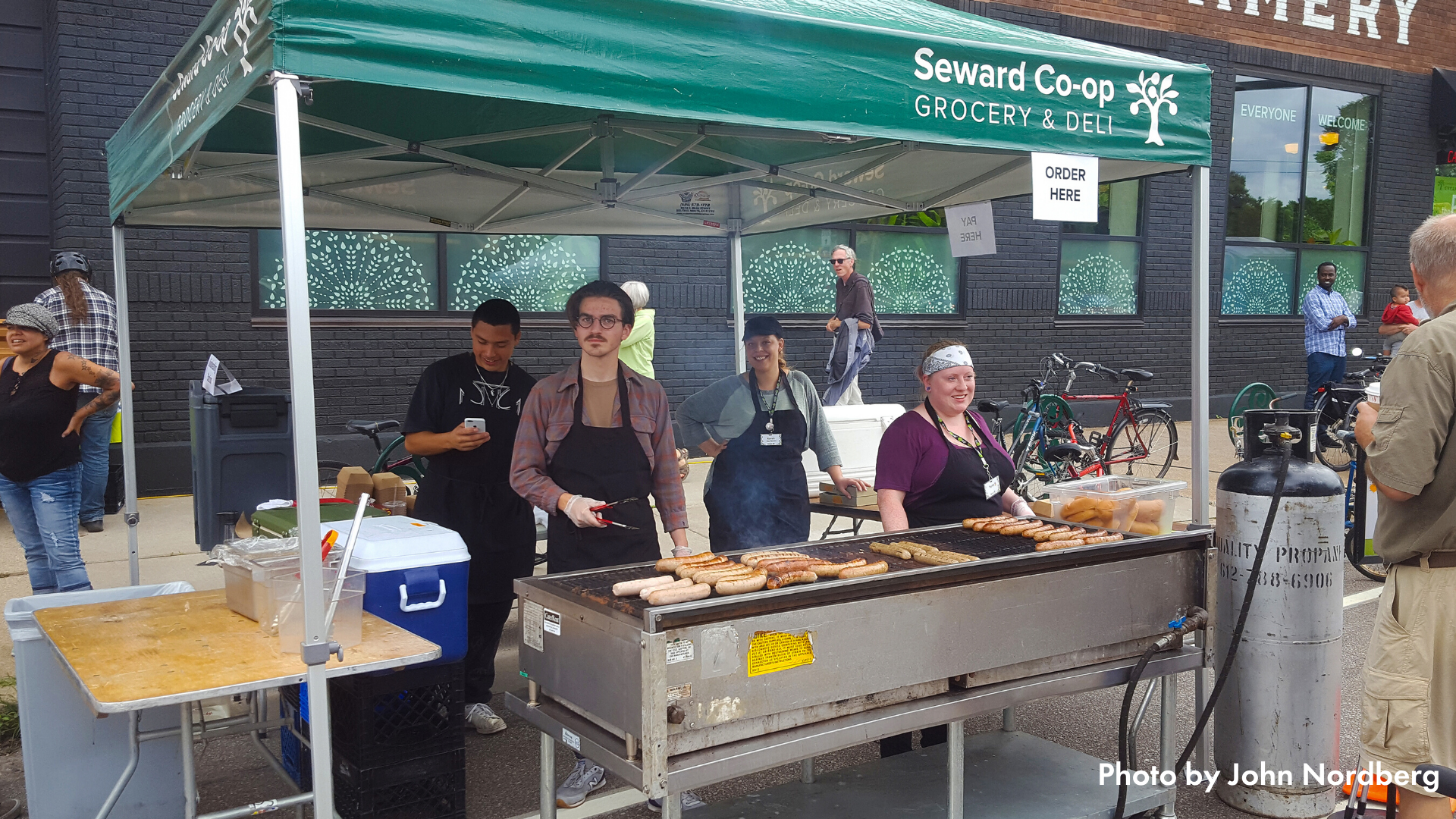Seward Co-op staff grilling under a pop-up tent at Open Streets Franklin