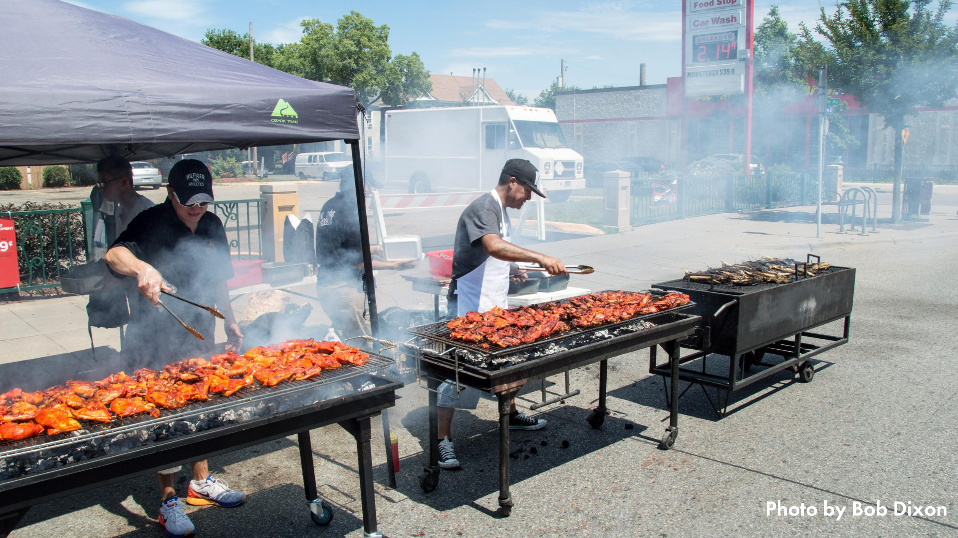 Two people grilling meat on three large grills at Open Streets East Lake