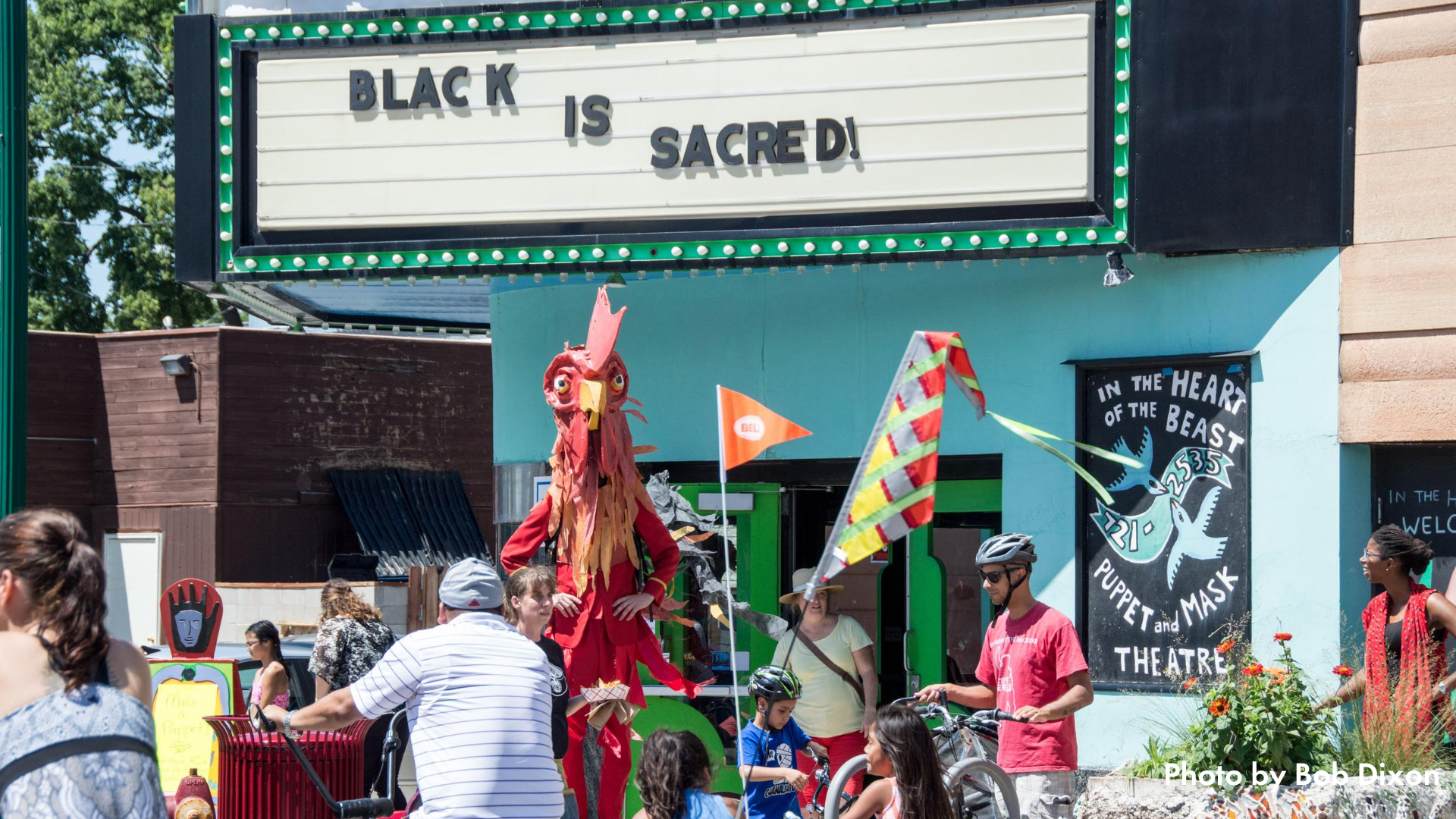 """Children and adults biking and walking in front of In the Heart of the Beast at Open Streets East Lake. The marquee reads """"Black is sacred!"""""""