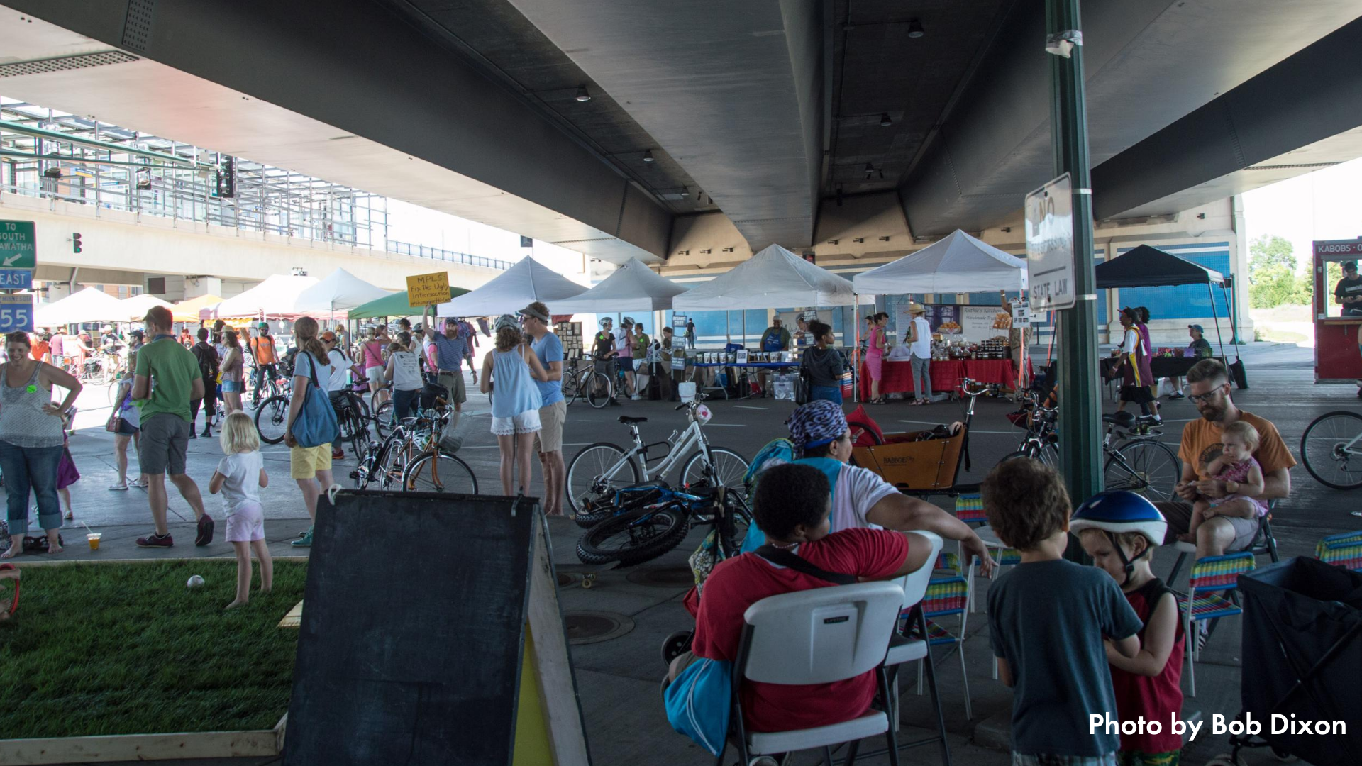 People shopping at a market set up under an overpass at Open Streets East Lake