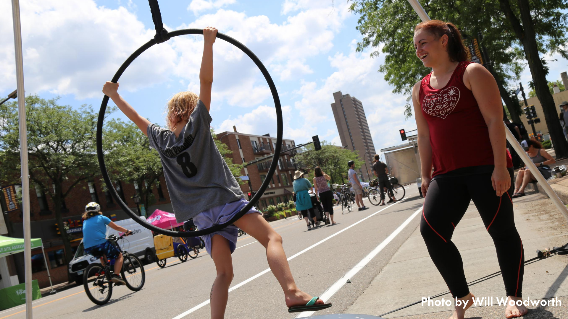 An adult supervising a child using a lyra at Open Streets Northeast
