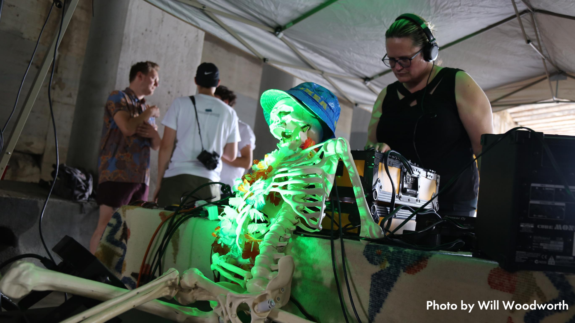 A DJ hosting a dance party in an underpass at Open Streets Northeast. A fake skeleton rests on the front of the DJ's table