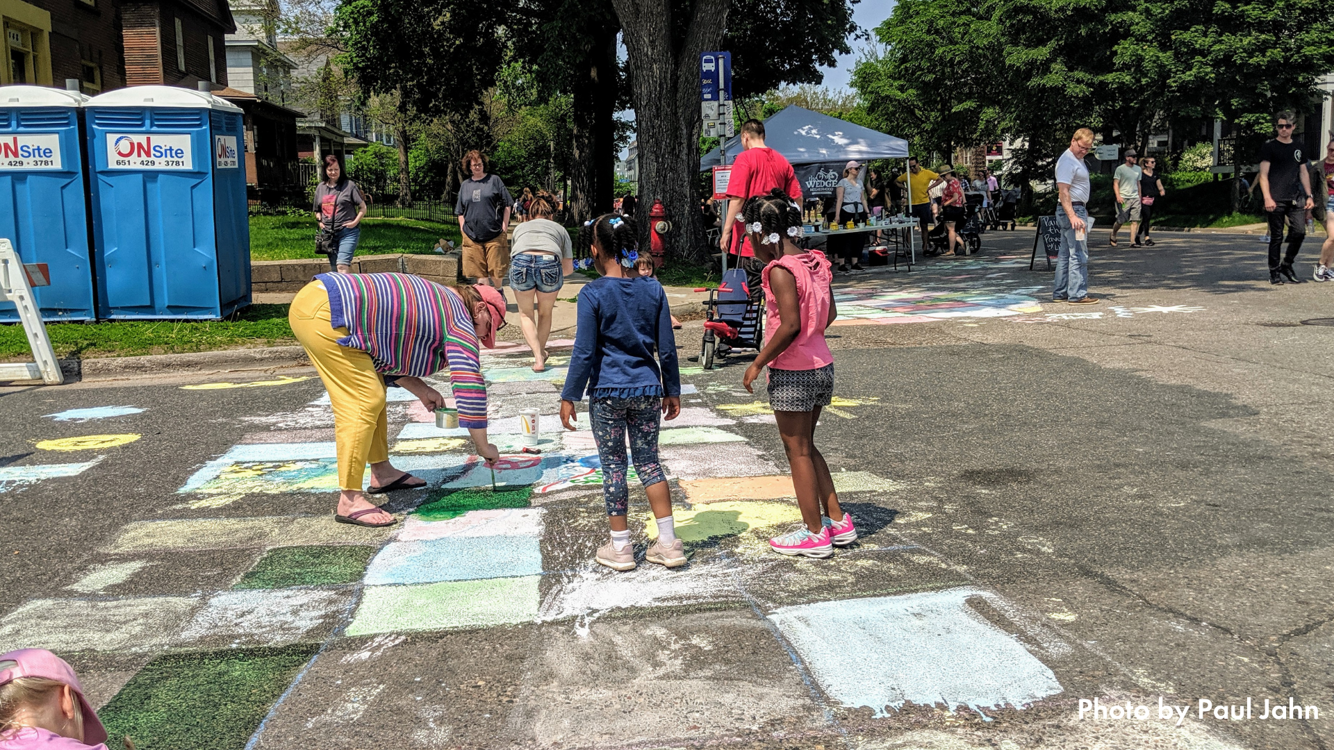 An adult and two children using chalk to make an art crosswalk at Open Streets Lyndale