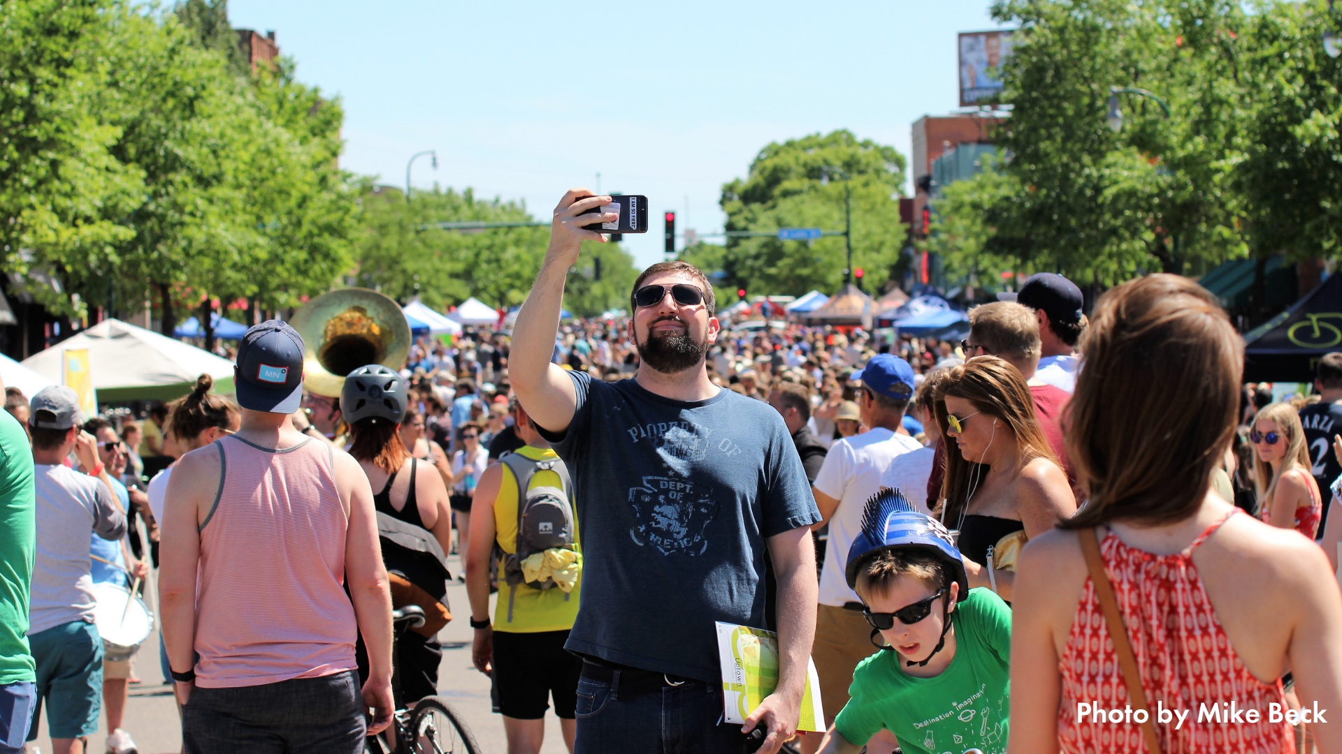 A person takes a selfie in the middle of a large crowd at Open Streets Lyndale