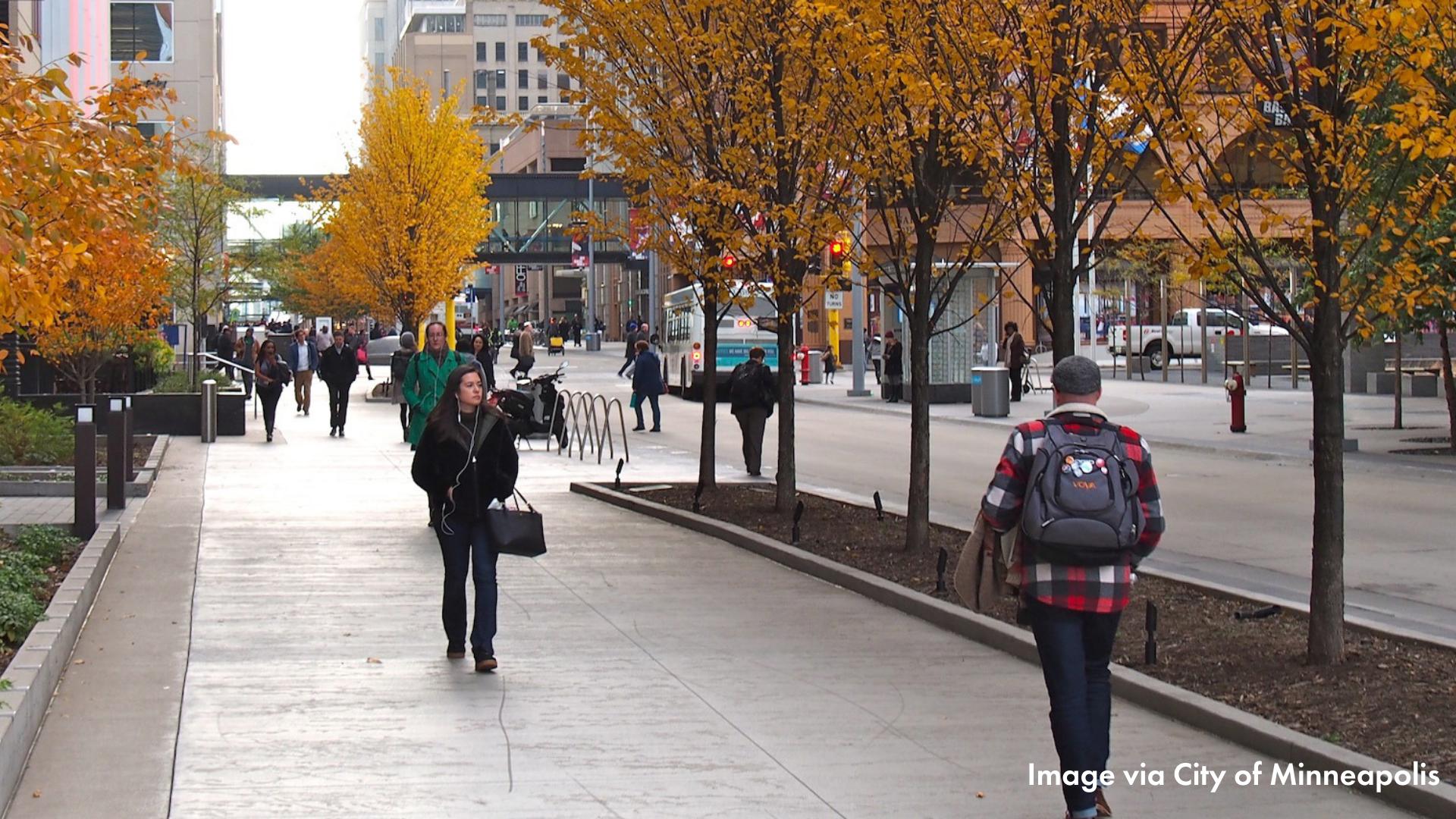 People walking on a wide sidewalk in downtown Minneapolis