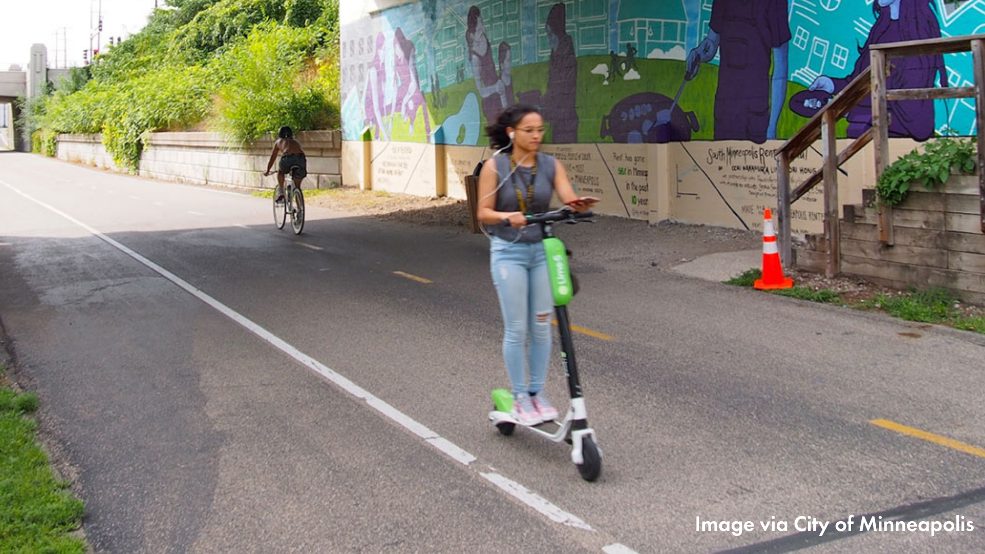 A person riding an electric scooter on the Midtown Greenway. There is a mural in the background.