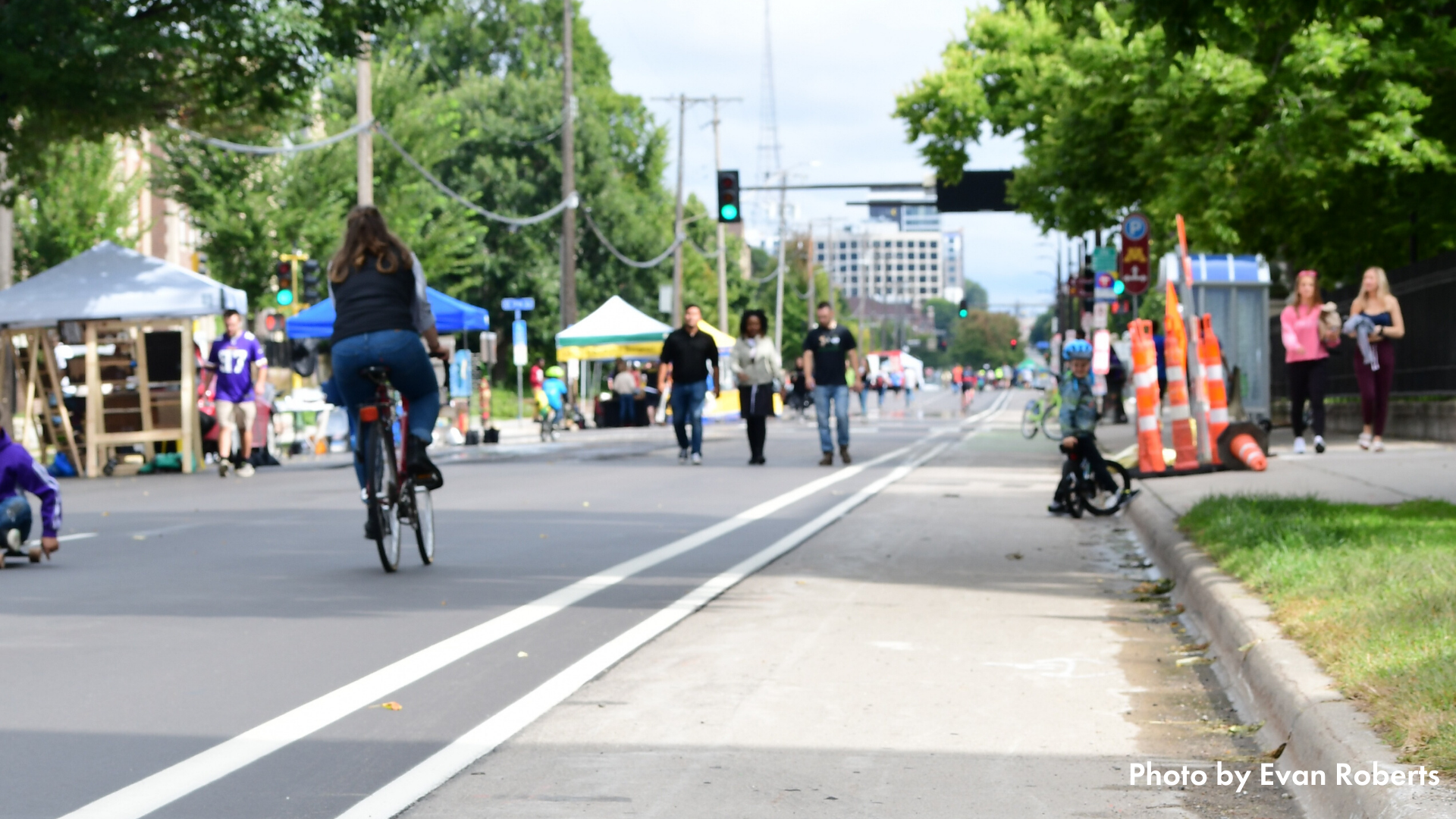 A photo of an Open Streets Minneapolis event taken at a low angle. In the foreground is a painted bike lane, in the background there are people biking & walking