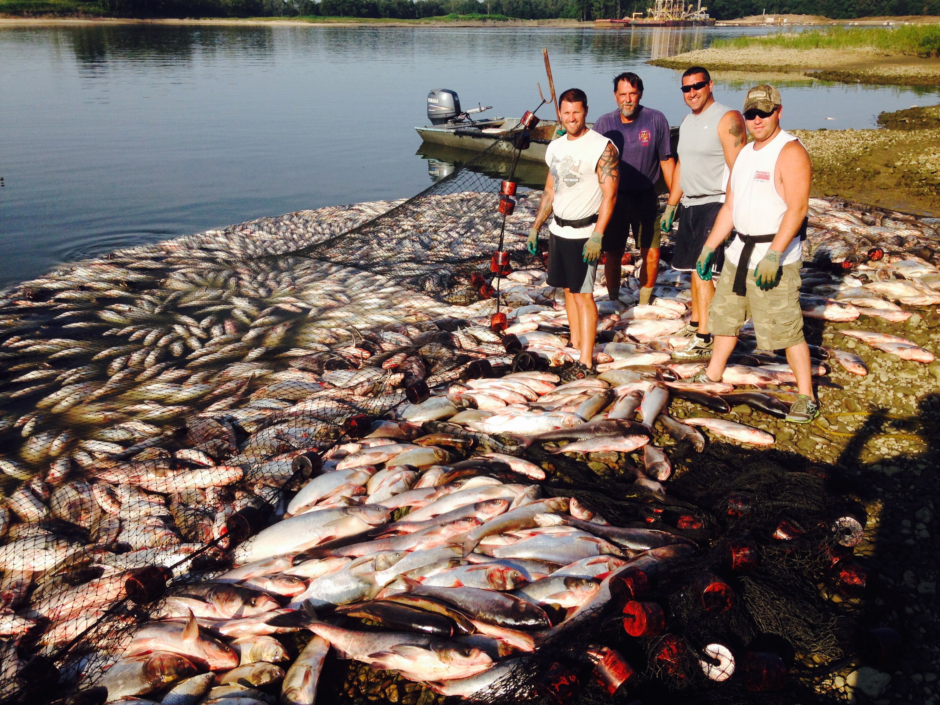 Commercial anglers stand with their catch following an Asian carp removal effort on the Illinois River last week, which employees from the Michigan DNR assisted with.