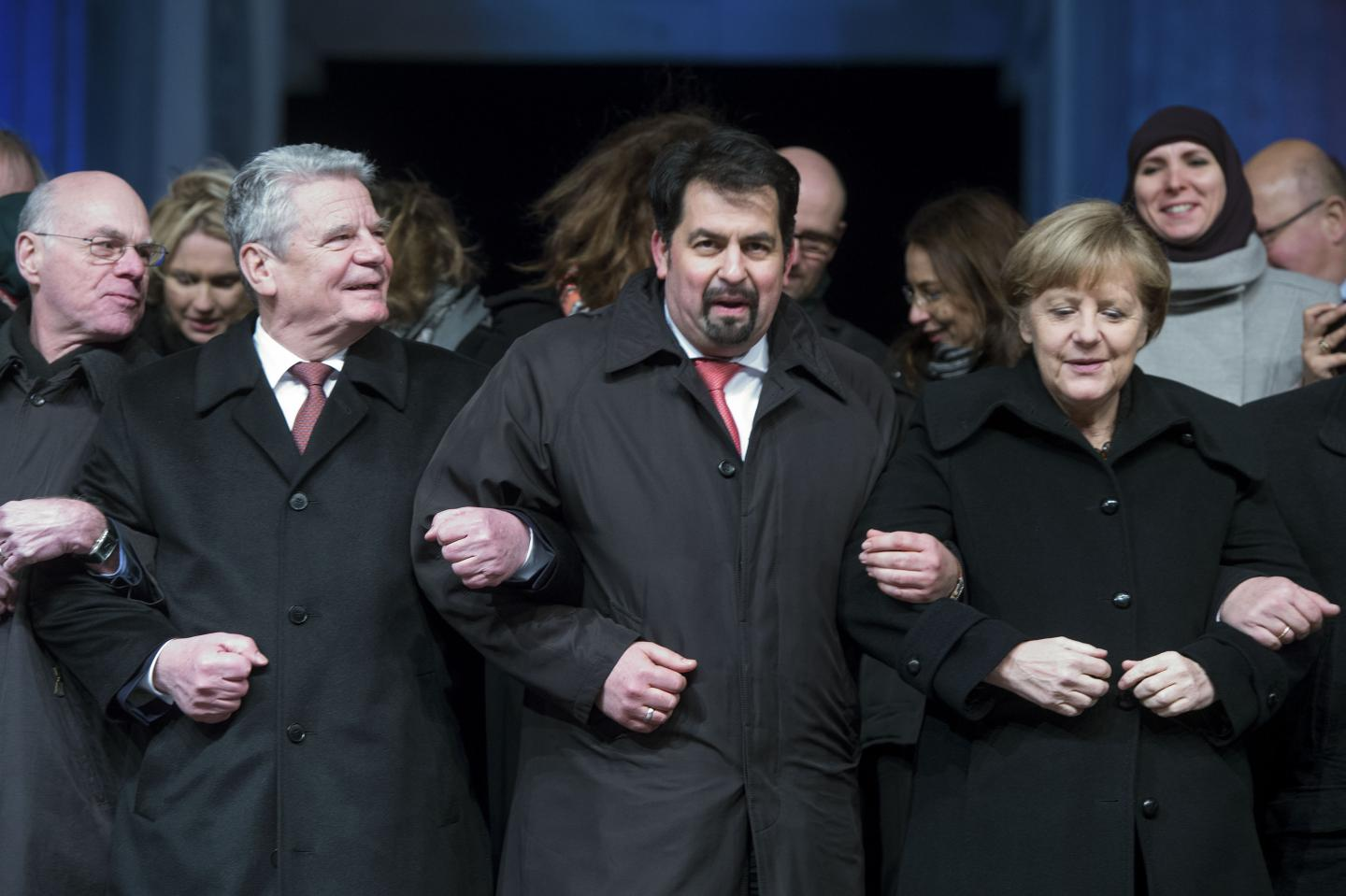 Chairman of the Central Council of Muslims in Germany Aiman Mazyek and German Chancellor Angela Merkel link arms with other officials during a vigil organised by Muslim groups for the victims of a shooting by gunmen at the offices of the French satirical weekly newspaper Charlie Hebdo, in front of the Brandenburg Gate in Berlin January 13, 2015. Mazyek has recently said that discrimination against Jews or any race is a sin in Islam.