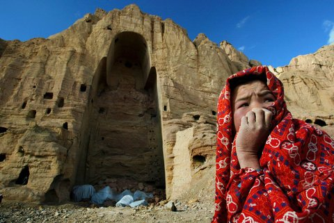 An Afghan girl who lived in the caves of Bamiyan sat in front of the ruins of a Buddha statue that the Taliban blew up the previous year. 2002.