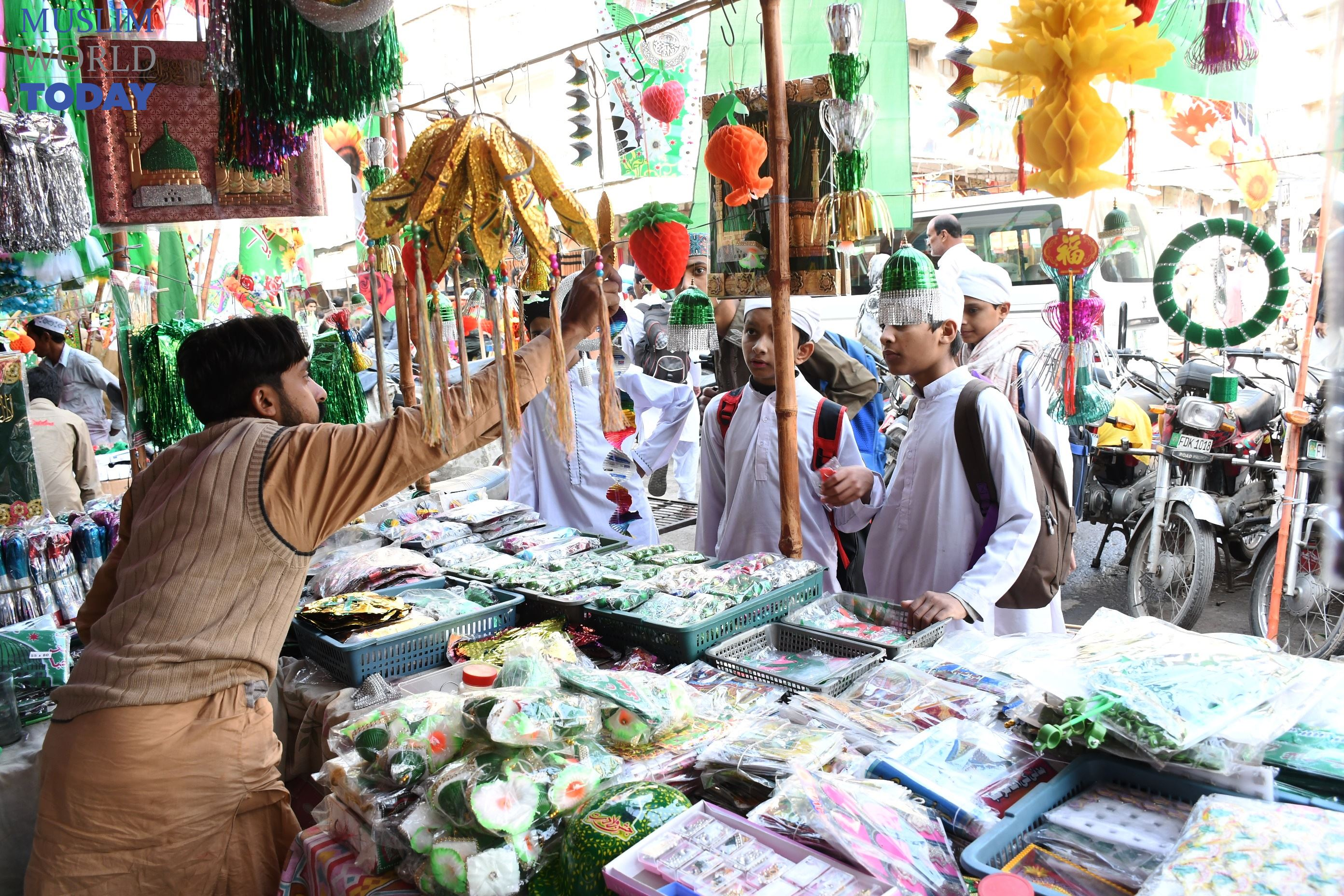Man sells souvenirs at a stall in Ghanta Ghar Bazar, Faisalabad, ahead of Eid Milad-un-Nabi