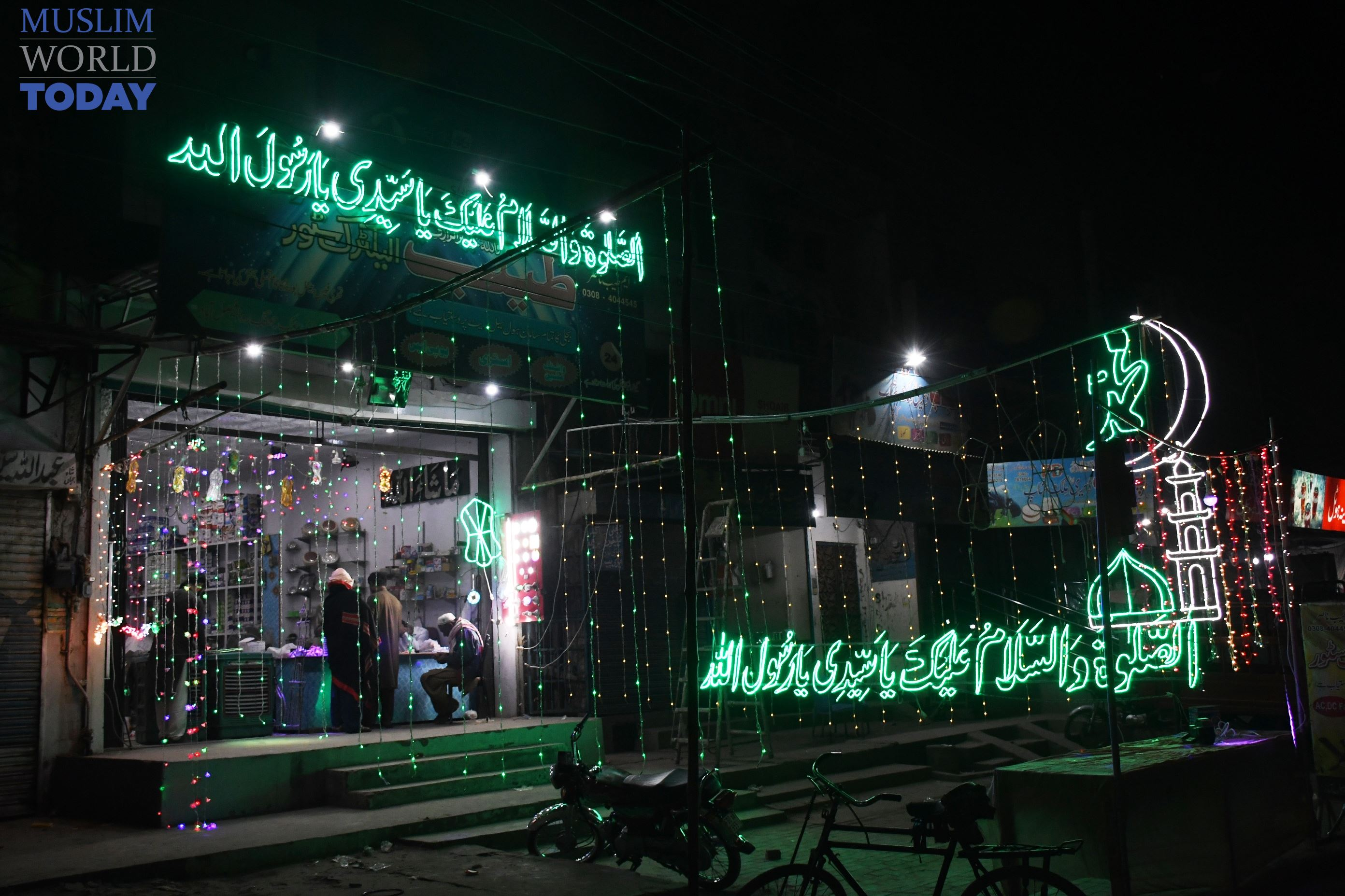 Lights brighten a stall with Islamic writings in Madina Town, Faisalabad