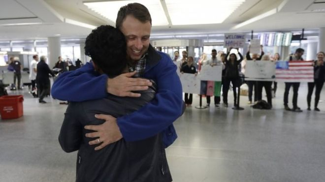 Army Captain Matthew Ball (R) hugs his former interpreter Qismat Amin at San Francisco International Airport.