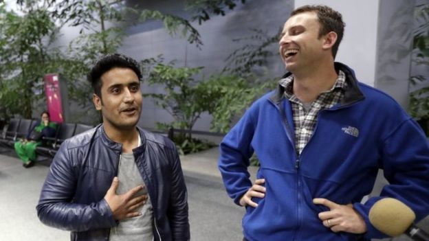 Army Captain Matthew Ball (R) laughs with his former interpreter Qismat Amin.