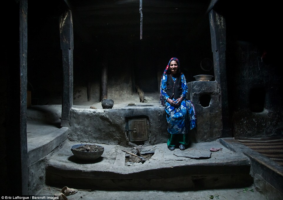 An Afghan woman in vibrant blue and green, inside her traditional Pamiri house, which is simply put together without luxuries