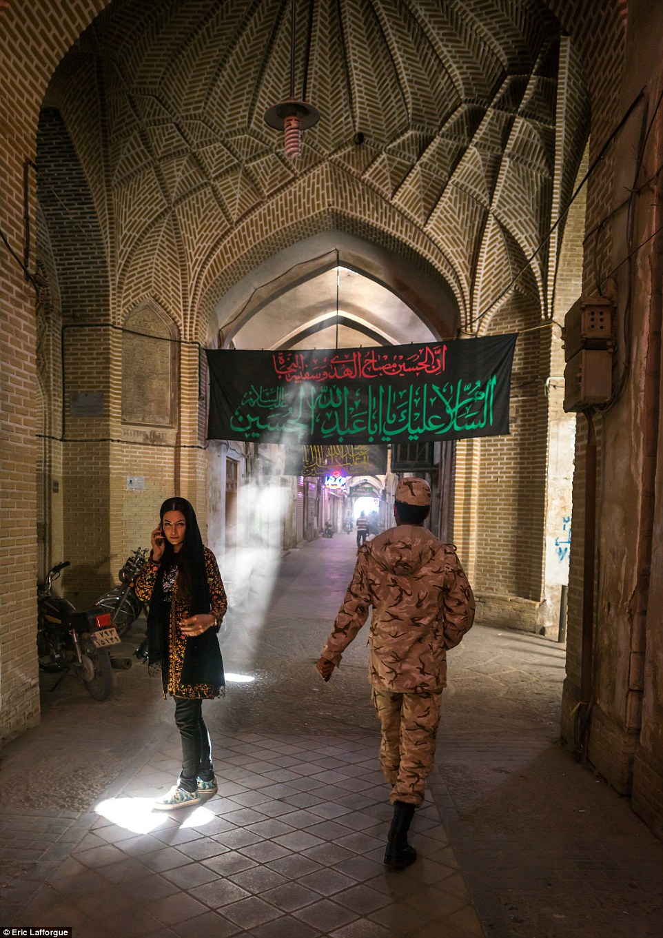 A woman and a soldier pass by each other in the bazaar in Yard, which is one of the oldest historical places in the central Iranian town