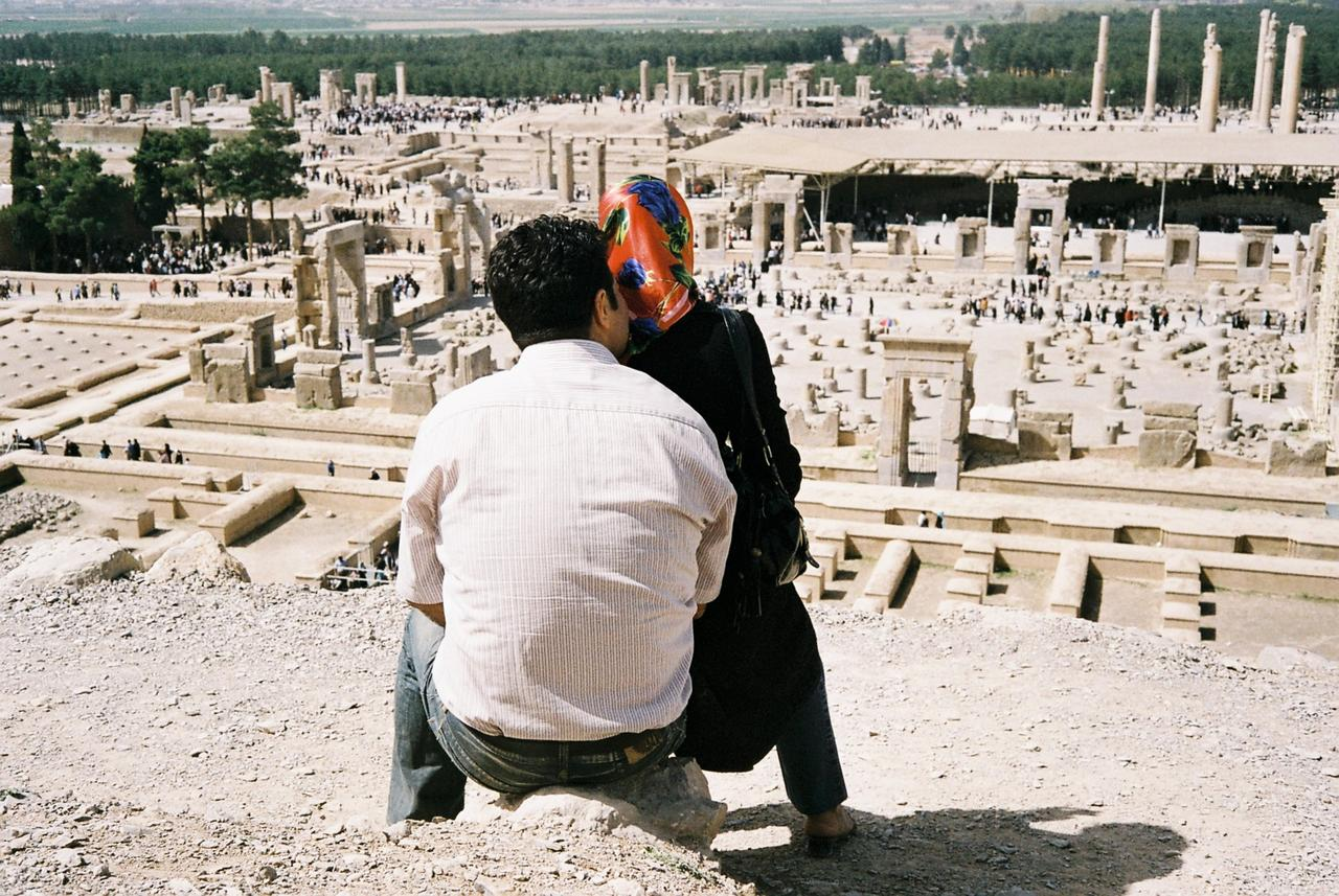 A young Iranian couple in the midst of a rare public embrace overlooking the ruins of Persepolis, the ceremonial capital of the Achaemenid Empire.