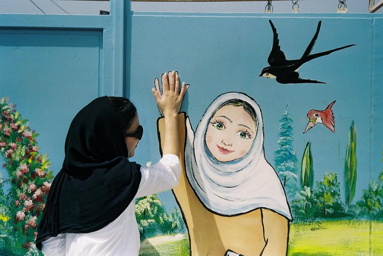 Gypsy at a mural painted on the gate of a girl's school in the city of Yazd.