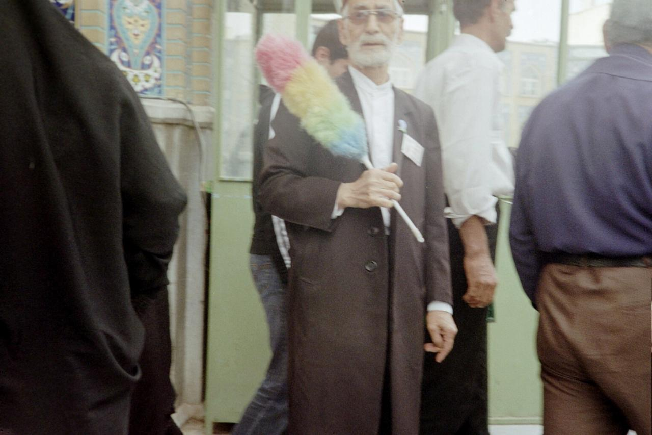 "A ""decency guard"" outside a mosque in the holy city of Qom, the largest center for Shia scholarship in the world. He uses the feather duster to touch the part of a woman he deems insufficiently covered."