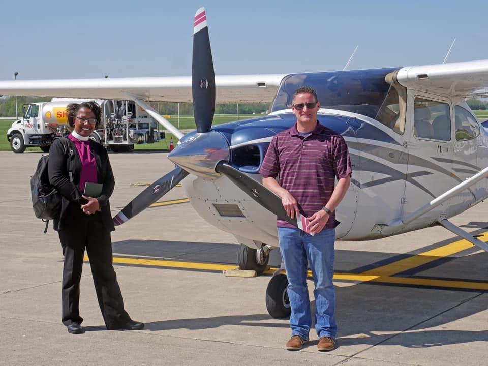 Bishop Jennifer Baskerville-Burrows and Marty pose with the plane following their PrayerFlight over Indianapolis and the surrounding suburbs.