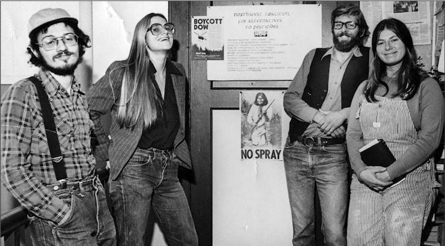"Black and white photo of 4 people involved in NCAP's early work, with ""No Spray"" poster in background."