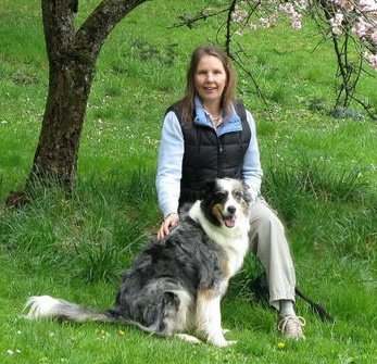 Olivia Thomas, Grants Manager, posing outside with her dog