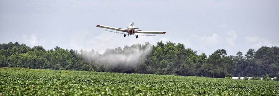 Airplane spraying pesticides over farm field