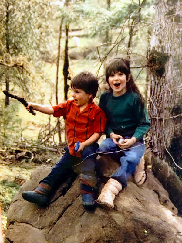 Ashley and her brother as children, on a rock in the woods