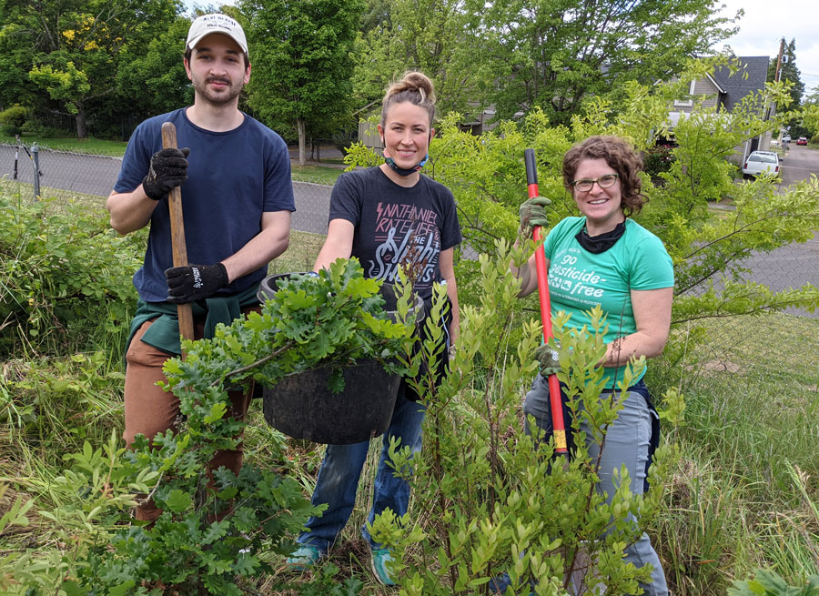 Three NCAP staff smile with tools and trees