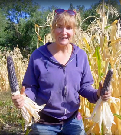 Casey O'Leary holding up two ears of corn, with corn plants in the background