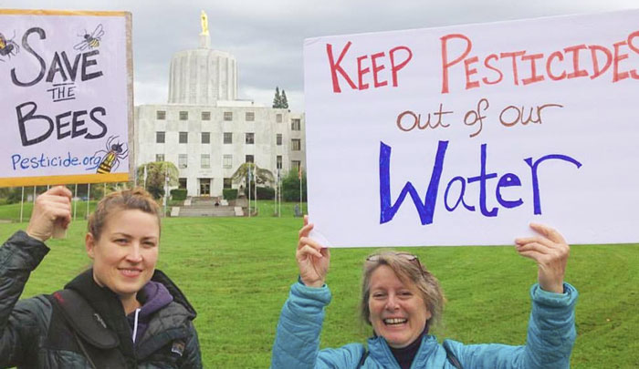 Two NCAP staff stand in front of the capitol building in Salem, OR holding up anti-pesticide signs