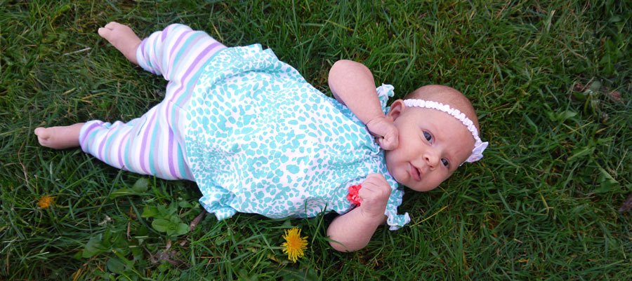 A baby lays in the grass, staring up at the viewer