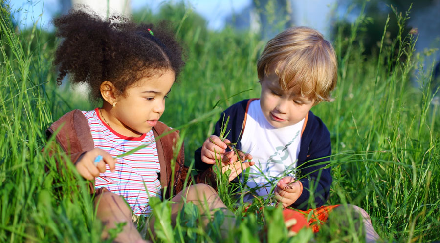 Two young children sitting in the grass