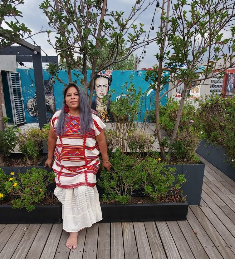 Image of Teresa with long light blue dyed hair in and outdoor setting. She has a long white dress on with red traditional Mexican embroidery. She is leaning bench smiling looking straight ahead with art work of Frida Khalo face behind her. There are tree in the background and wooden planked floor where she is standing barefoot.