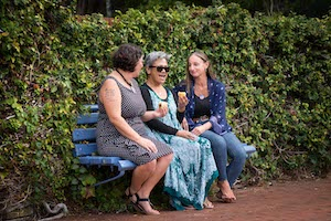 3 people sit talking on a park bench