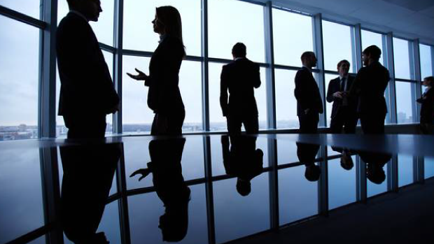 Image of women and men standing around in a boardroom