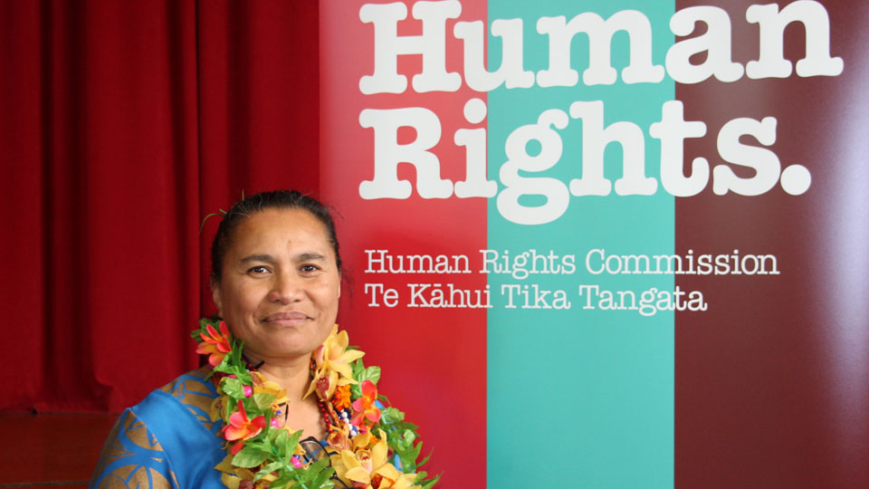 Picture of Karanina Sumeo standing in front of a human rights commission banner