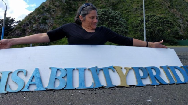 Person holding a Disability Pride sign