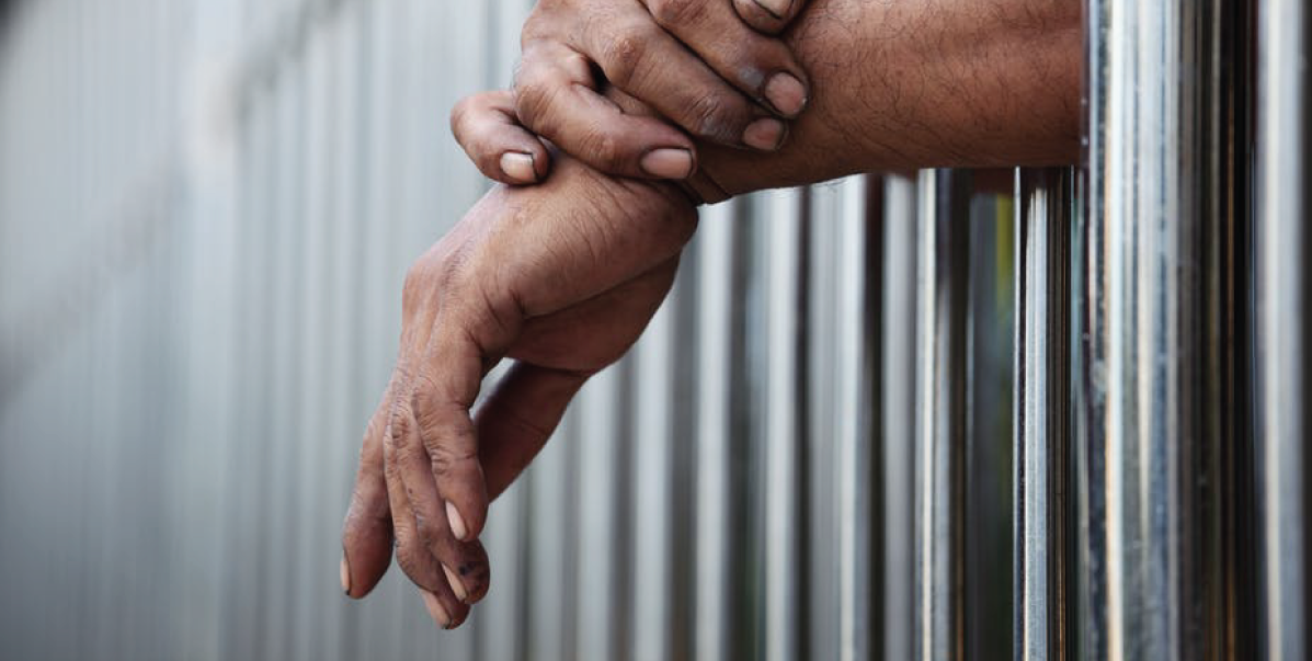 Hands coming out from beyond bars in a detention center