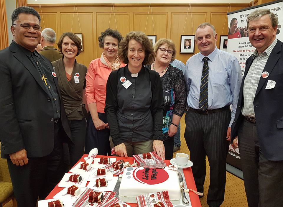 Living wage supporters stand around a table with LW cake