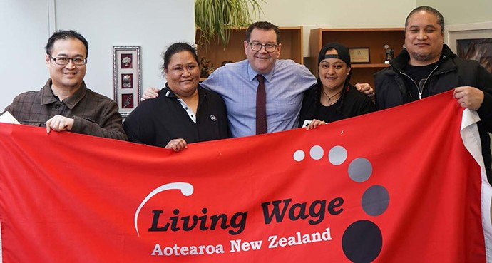 MP Grant Robertson with  Living Wage Advocates who are holding a Living Wage banner